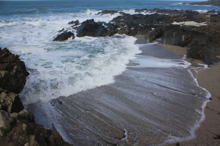 The waves rushing into a beach cove photo