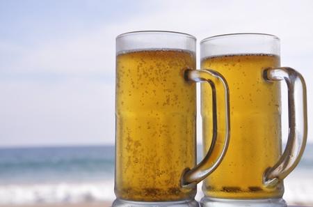 ビーチで晴れた日に冷えたビールの 2 つのマグカップ