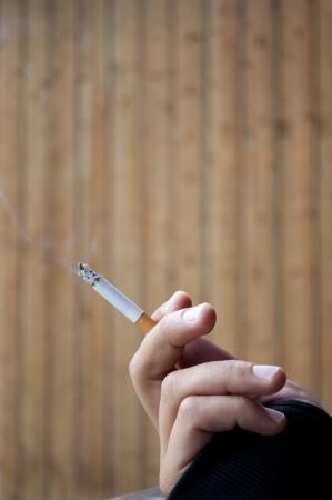 man smoking: A Man Smoking a Cigarette in Winter Stock Photo