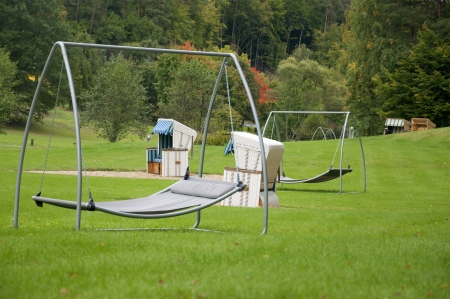 Beach Baskets or Strandkorbs and Swing Sunbeds Amidst Greenery in Germany in Autumn  Stock Photo