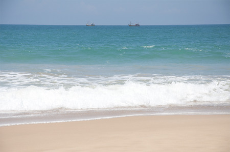 placid water: Boats sailing in the clear blue waters of the Indian Ocean on a bright sunny day in Sri Lanka