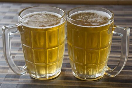 Two Mugs of Chilled Beer on a Table