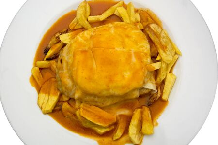 A classic francesinha (portuguese sandwich) in Porto, Portugal - made with bread, ham, pork, smoked sausage, bacon, steak and covered with melted cheese and a hot tomato and beer sauce