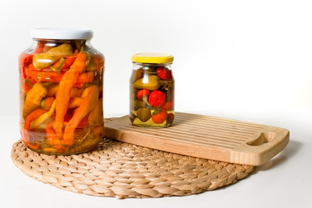 Two jars of paprika on cuting board Stock Photo