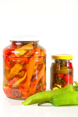 Two jars of paprika with fresh vegetables