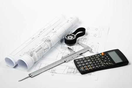 caliper on blueprint with calculator