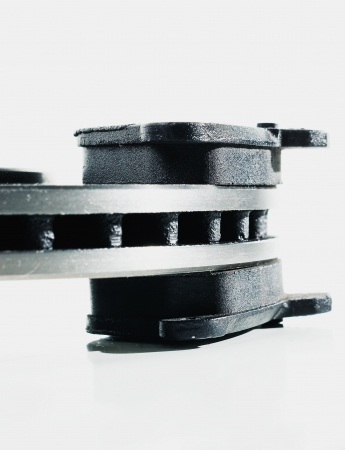 brake disc: Two brake pads and one brake disc isolated on white