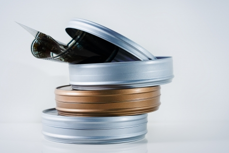 Three 35mm film tins isolated with film reel Stock Photo