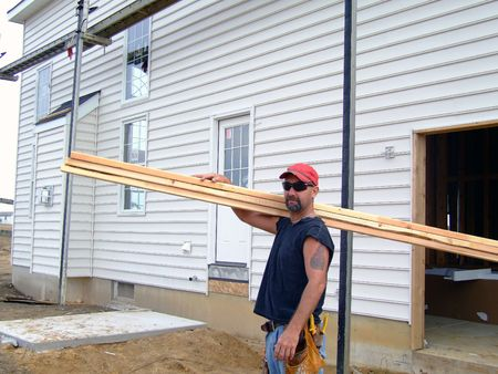 Construction Worker - Carrying Lumber Stock Photo