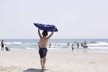 Boy running to ocean with raft