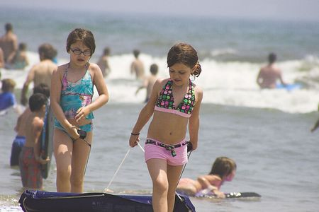 Two girls on beach with raft Stock Photo