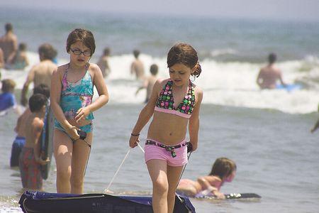 Two girls on beach with raft Reklamní fotografie