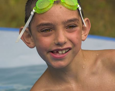 wet boy in pool with goggles