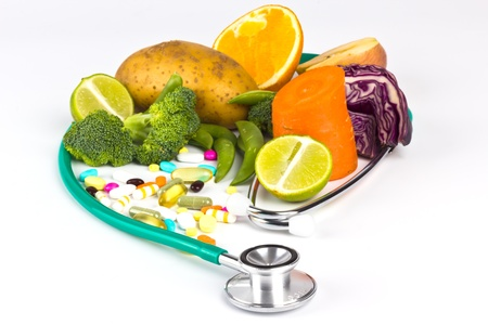 stethoscope around assorted natural food vegetable fruit and pills