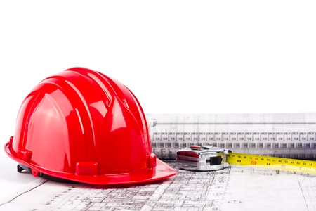 red hard hat and measuring tape put on blueprint on wihte background