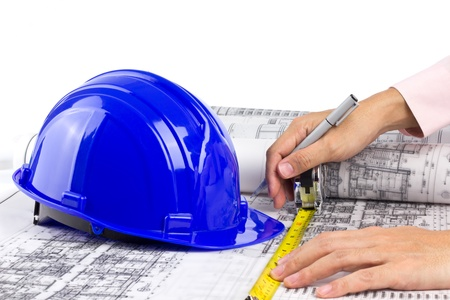 architect hand pull measuring tape and writing on blueprint near hard hat, white background