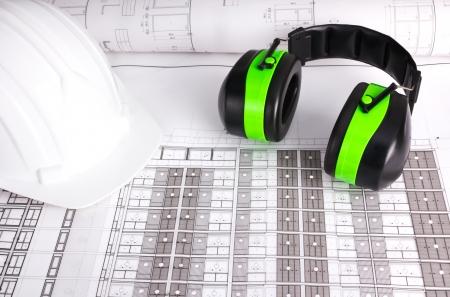 White hard hat and green earmuffs put on blueprint Stock Photo - 14329010