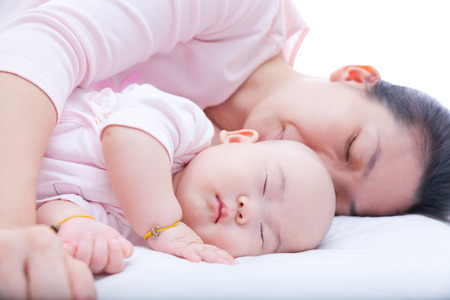 Young woman embrace her newborn daughter sleeping in the bed Archivio Fotografico