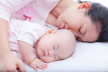 Young woman embrace her newborn daughter sleeping in the bed Stock Photo