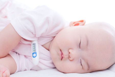 Close-up newborn baby sleeping in bed with digital mercury thermometer photo