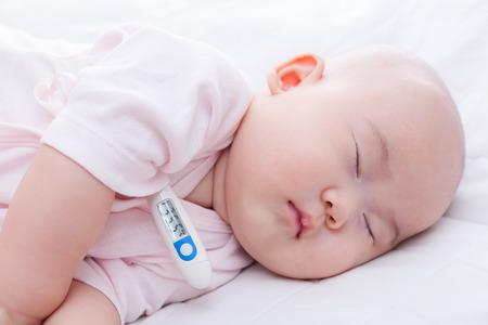 Close-up newborn baby sleeping with digital mercury thermometer