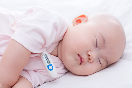Close-up newborn baby sleeping with digital mercury thermometer Stock Photo - 32122676