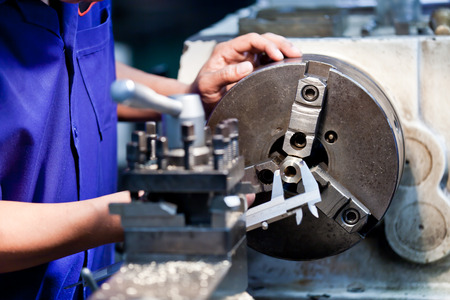 mechanician: Milling machine operator working in factory workshop