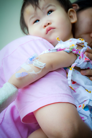 Mother carrying her baby sick in hospital,shallow DOF saline intravenous (IV) in focus ,face out of focus photo