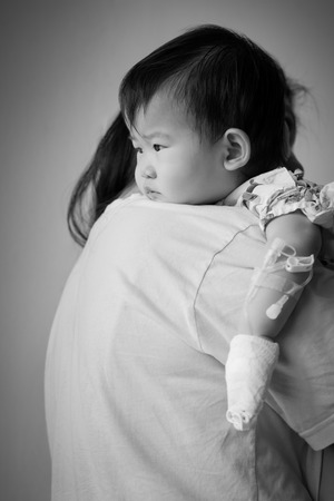 asian baby girl: Mother carrying her baby sick in hospital,saline intravenous (IV) on hand baby ,black&white picture