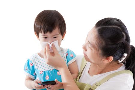 malato: Madre asiatica che trasportano e soffiando il naso sua figlia, bambino in possesso di gadget elettronici, isolato su sfondo bianco