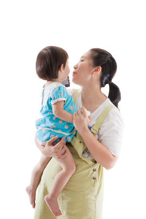 soothe: Asian mother carrying  and soothe her daughter,child holding electronic gadget ,isolated on white background Stock Photo