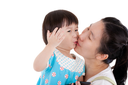 smooching: Asian mother carrying and smooching  her daughter,child holding electronic gadget ,isolated on white background Stock Photo