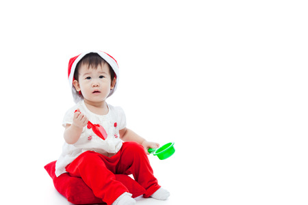 Christmas little girl sitting on pillow and waiting in santa hat ,Isolated on white background