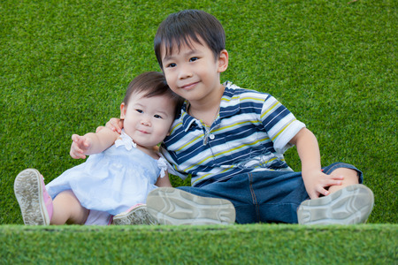 Brother and sister sitting and smiling on grass photo