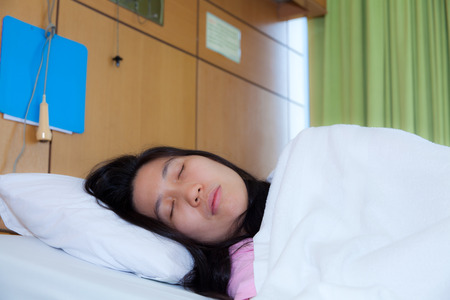sickbed: Asian woman patient lying on a sickbed in hospital ward Stock Photo