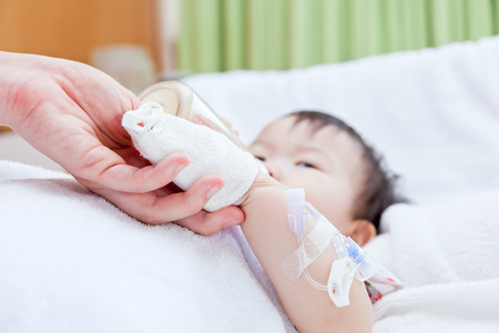 sickbed: Woman holding baby hand, little asian girl lying and suck up milk on a sickbed, saline intravenous (IV) on hand, shallow depth of field (DOF) saline intravenous (IV) in focus, face out of focus Stock Photo