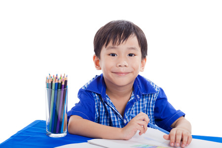 Happy asian boy smiling and sitting at the table and drawing by color pencil isolated on white background photo
