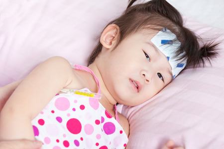 Close-up little asian girl lying with mercury thermometer and jel cooling patch, a thermometer between armpit Фото со стока
