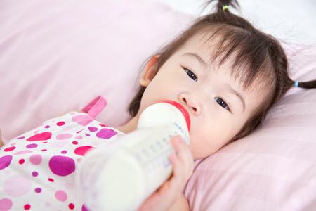 nursing bottle: Beautiful little asian girl lying and suck up milk bottle in bed Stock Photo