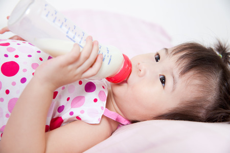 nursing bottle: Beautiful little asian girl lying and suck up milk bottle in bed Stock Photo