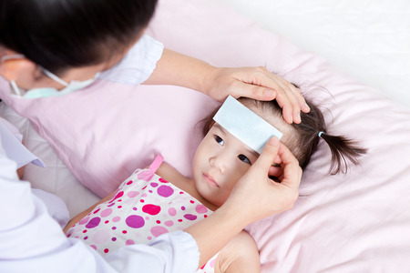 sickbed: Portrait of confident female doctor paste cooling fever patch on forehead little asian girl during medical treatment, girl lying on sickbed Stock Photo