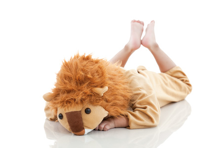 prone: Little asian child costumed and acting like a lion on floor with shadow reflection, child lying prone on floor, shot in studio, isolated on white background