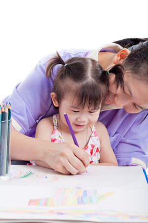 parental love: Portrait of woman and little asian girl drawing, painting and smiling together, mother teaches her daughter to draw with colour pencils , isolated on white background