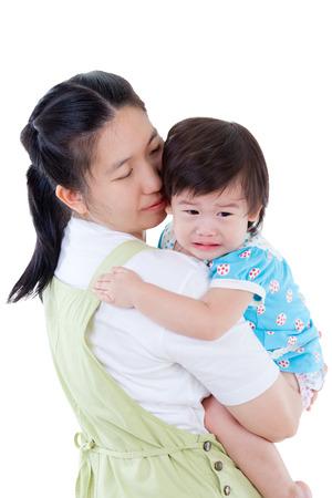 bebe enfermo: Madre asiática que lleva y calmar a su hija, niño llorando, aislado en fondo blanco