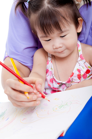 Portrait of woman and little asian girl drawing and painting together, mother teach her daughter to draw with colour pencil Stock Photo