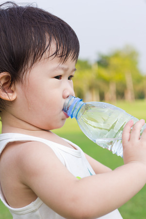 romp: Little asian girl  drinking water from plastic bottle, after tired from a romp in the park, outdoor shot