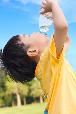 romp: Little asian boy drinking water from plastic bottle with the thirsty, after tired from a romp in the park, under bright sunlight and blue sky background, outdoor shot Stock Photo