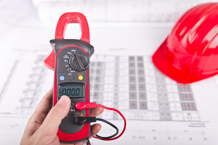 impedance: Hand of technician holding digital clamp multimeter over blueprint and red hard hat background