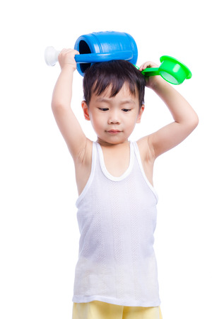 white singlet: Portrait of a little asian boy (thai) holding scoop sand and plastic watering can over head, child in a white singlet, , isolated on white background Stock Photo