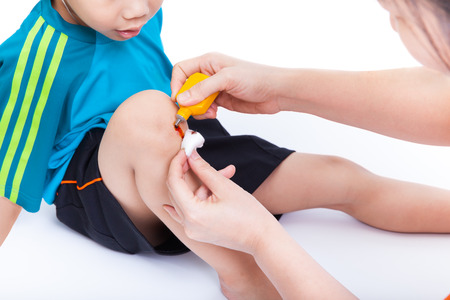 Little asian boy looking wound his leg, Mother provides first aid, on white background Stock Photo